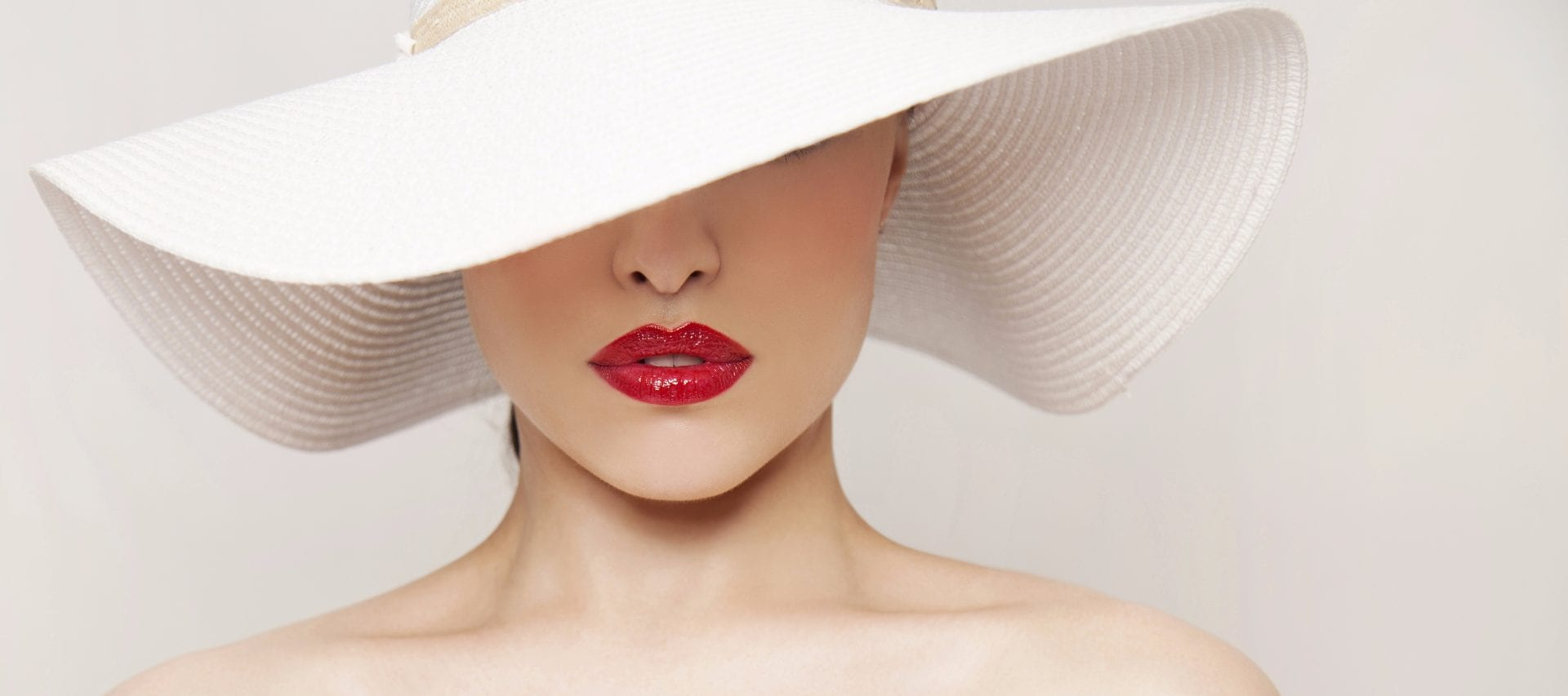 woman in stylish white hat which covers her eyes