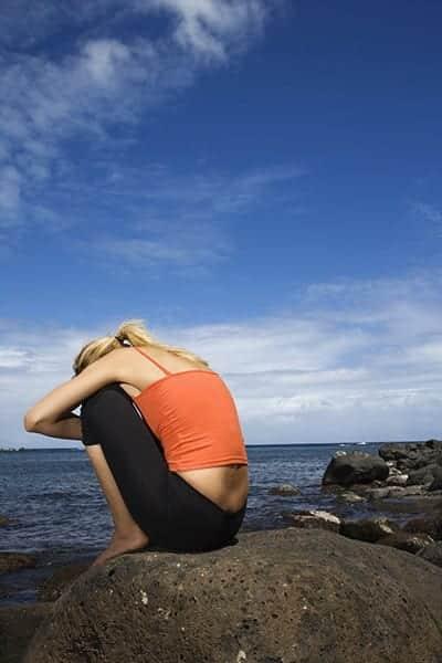 Upset woman sitting on rocky shore.